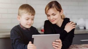 Mother helping son with teletherapy as facilitator