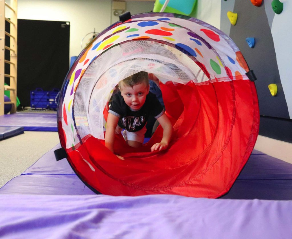 young boy crawling through tube at Carolina Therapy Connection