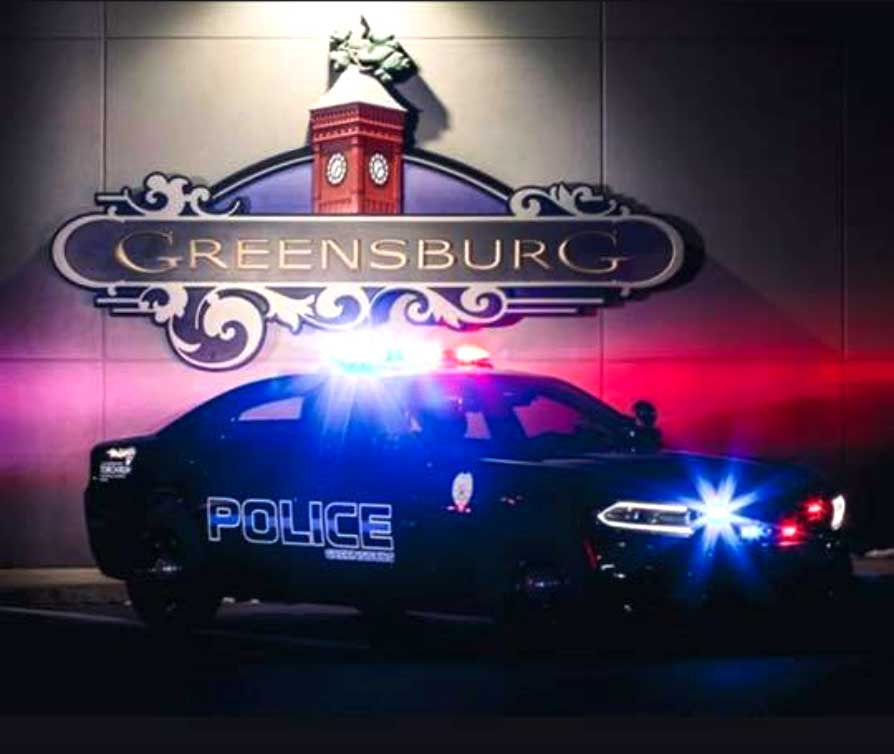 Greensburg police car in front of town sign