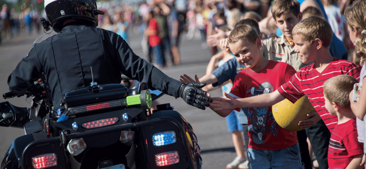 Mesa PD motor cop high fiving kids