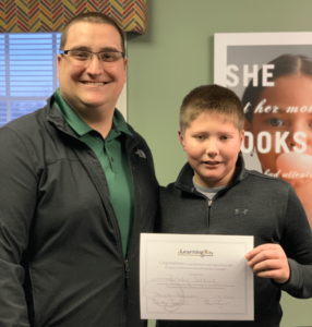 LearningRx Staunton-Harrisonburg: Male staff member with boy student getting a certificate