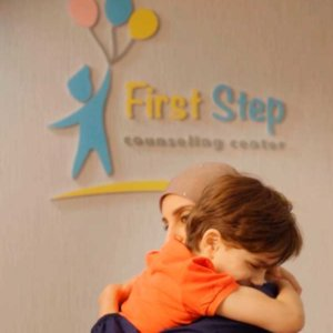 First Step staff hugging young boy