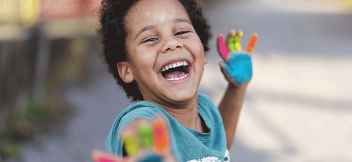 Smiling boy with paint on his hands