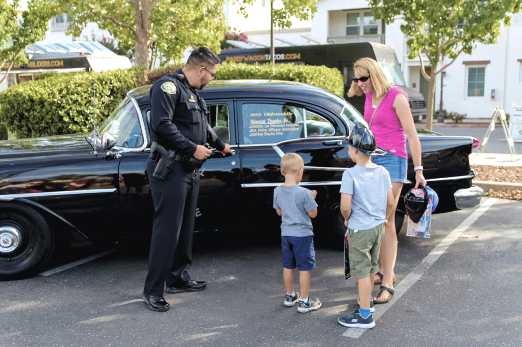 Morgan Hill Police officer showing off car to family