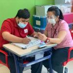 Athena Center teacher helping older student